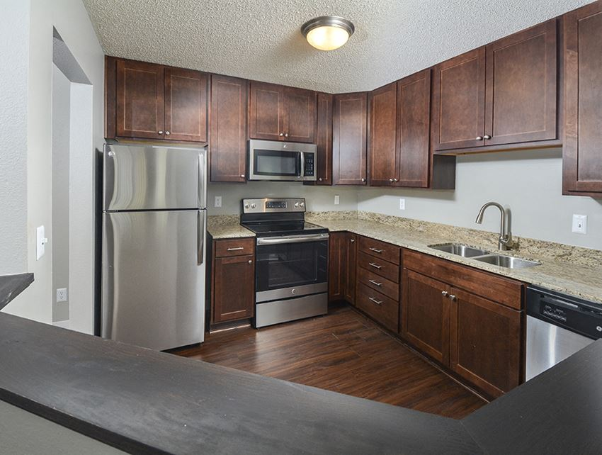 Renovated Kitchen with Stainless Steel Appliances, Granite Countertops and Dark Wood Cabinetry