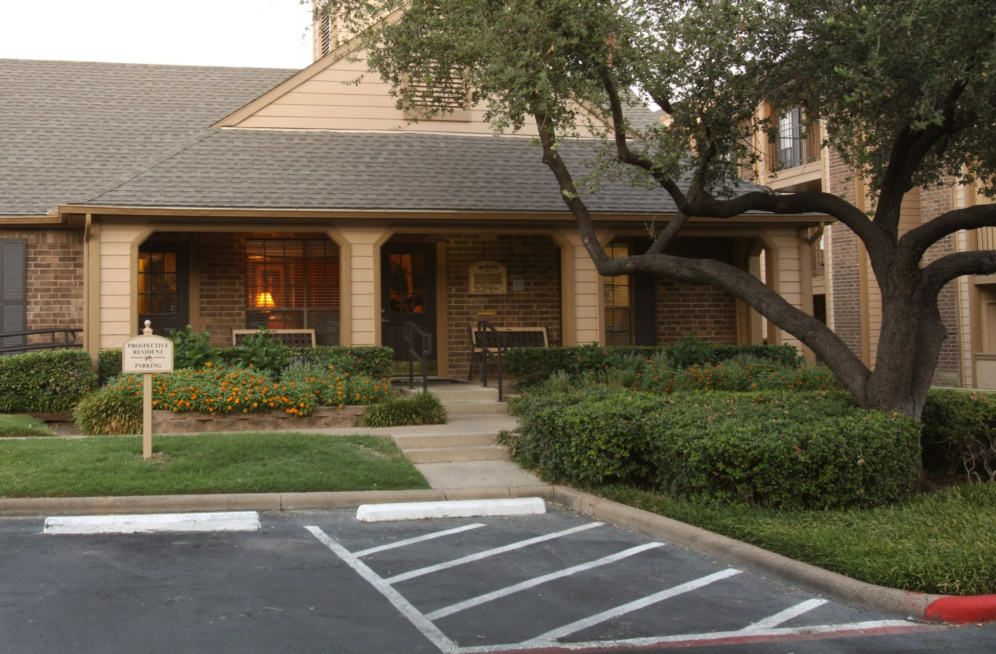 Clubhouse exterior, green trees, bushes, and parking lot