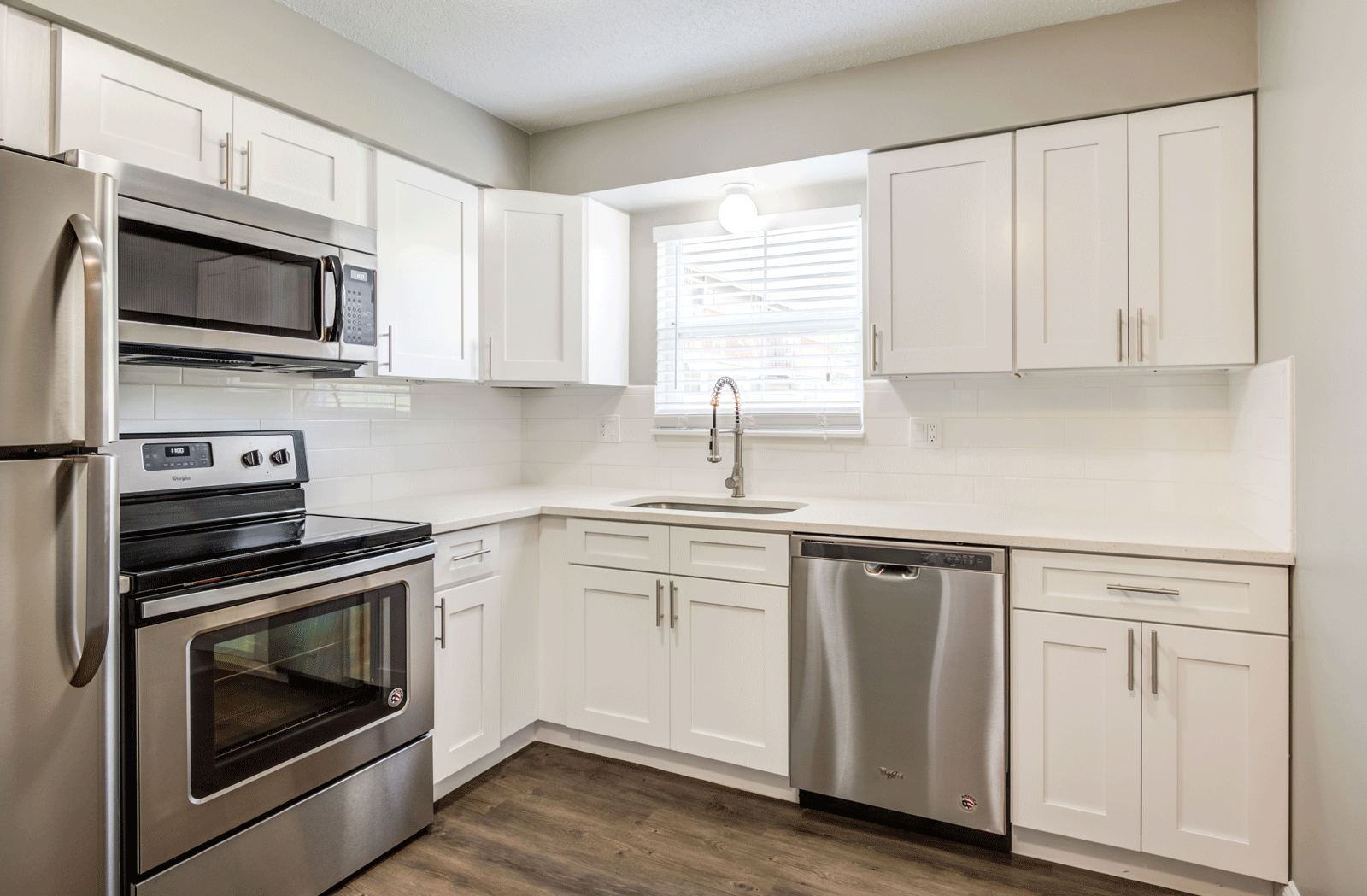 Updated kitchen with stainless steel appliances, white kitchen cabinets