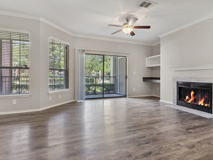 Pet Friendly Apartments in Plano, TX - Carrington Park Apartments Living Room With Fireplace, Ceiling Fan, Hardwood Style Flooring and Access to Outside Patio With Sliding Glass Door
