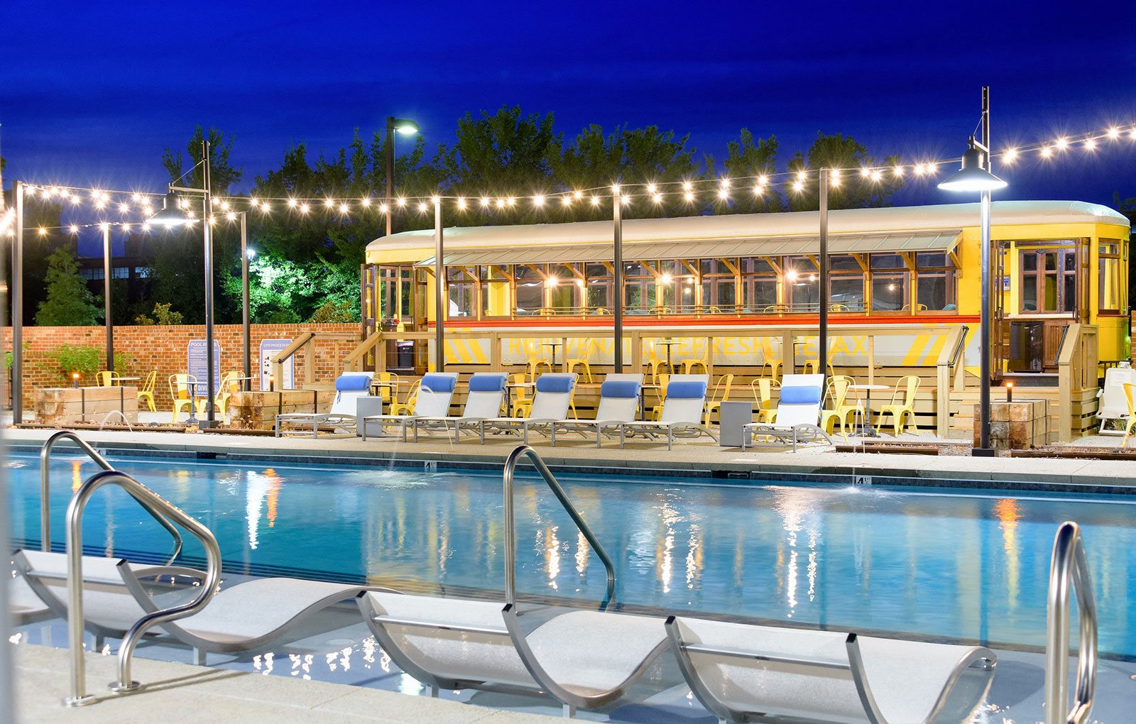 Resort Style Swimming Pool with Sun Shelf and Poolside Patio Seating in Trolley at Bluebird Row Southside Apartments, Chattanooga, TN 37408