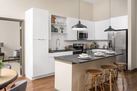 Bright White Kitchens with Side by Side Fridge, Granite Countertop, Designer Ceramic Tile Backsplash and Glass Top Ranges at Bluebird Row Southside Apartments, Chattanooga, TN 37408