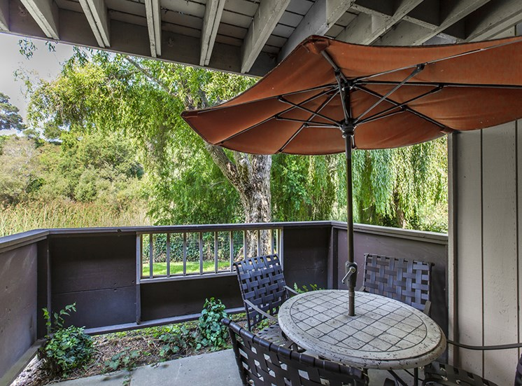 Patio with chairs, table, orange umbrella, small gardening plot, railing with view of tree and lush foliage.