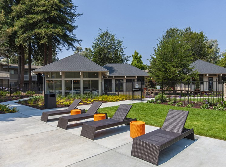 Concrete pool deck with brown deck chairs and orange tables. Grass, club house and lounge behind them.