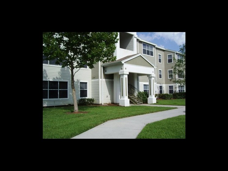 exterior of apartment building and sidewalk_The Crossings at Cape Coral Cape Coral, FL