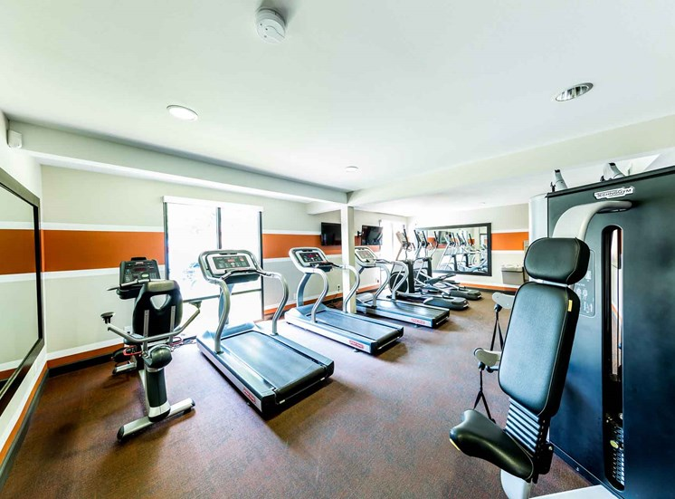 Fitness center with treadmills, exercise bikes, and strength training machines