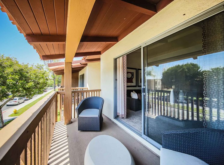 Sunny balcony with patio furniture and large sliding glass door