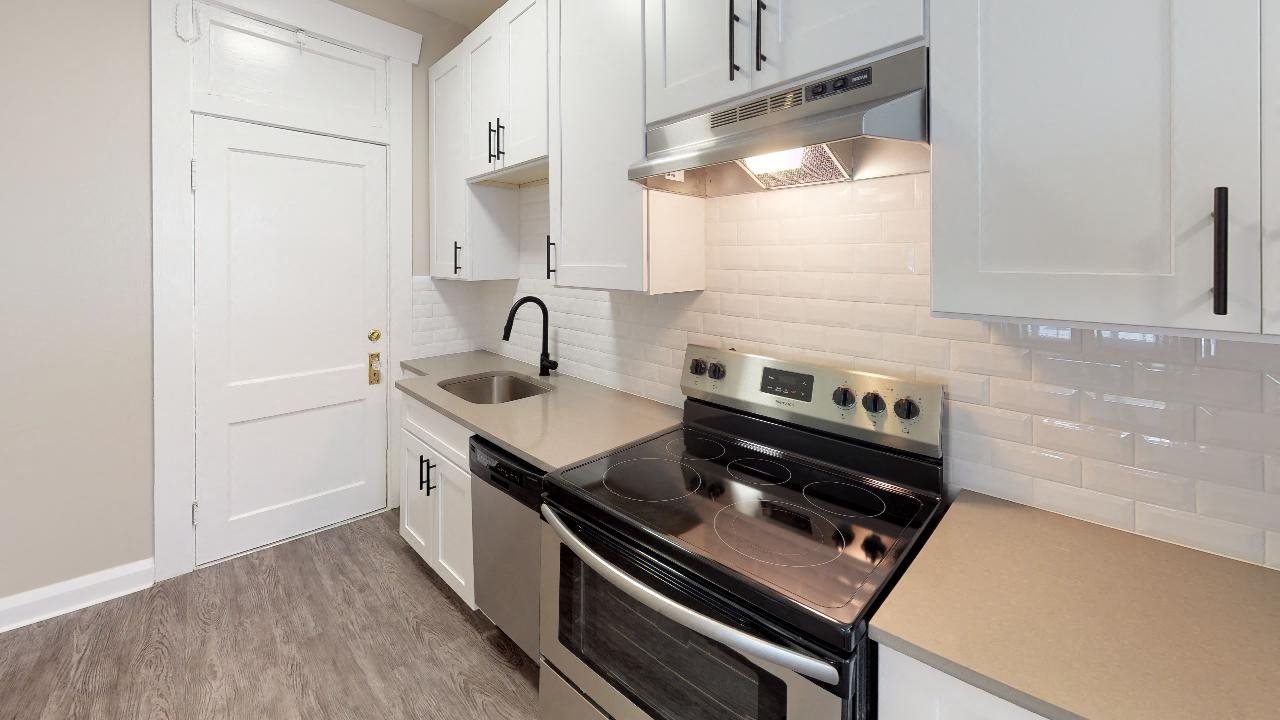 Studio kitchen with stainless steel appliances and subway tiled backsplash