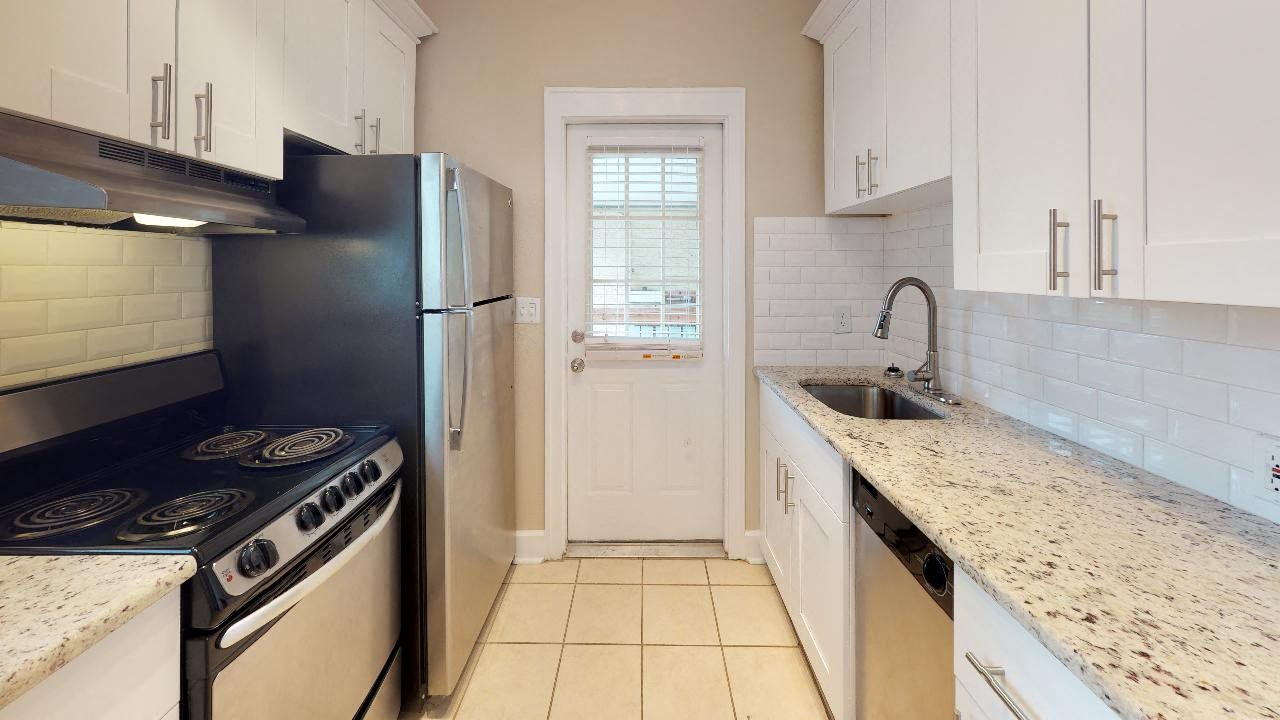 Upgraded kitchen with subway tiled backsplash