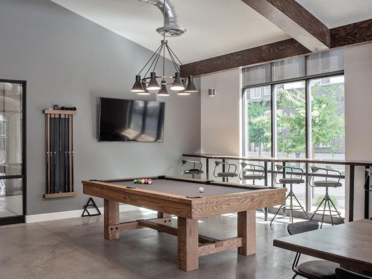 Clubhouse pool table, bar seating and wall tv from a different angle