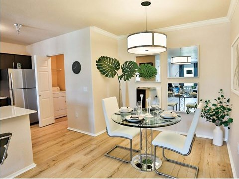 The Highland Apartments dining room with hanging light fixture and faux wood floors
