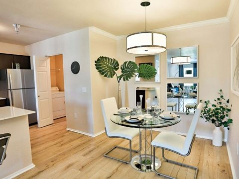 The Highland Apartments dining room and kitchen with light faux wood flooring