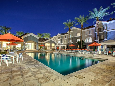 The Highland Apartments Pool as sunset with lounge seating, umbrellas, and palm trees