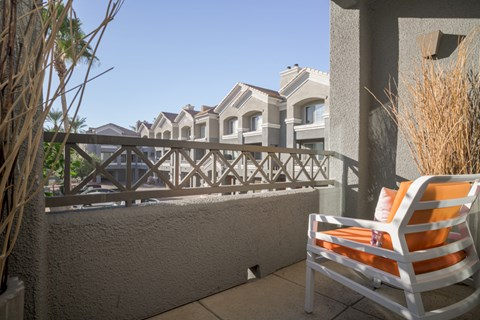 model balcony with views of the community and an orange chair