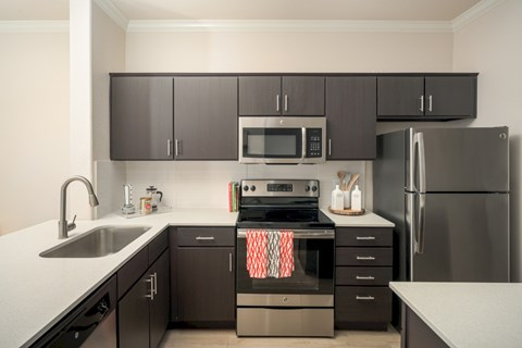 Model kitchen with dark brown cabinets, white quartz countertops, and stainless steel appliances