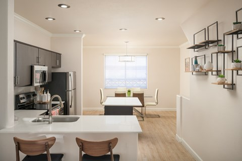 model kitchen looking to dining room with white quartz cabinets, dark cabinets and light faux wood floors