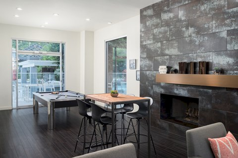 game room with pool table, table, and fireplace