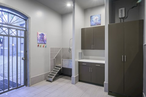 Pet Wash Station with white floors, brown cabinets and door to outside