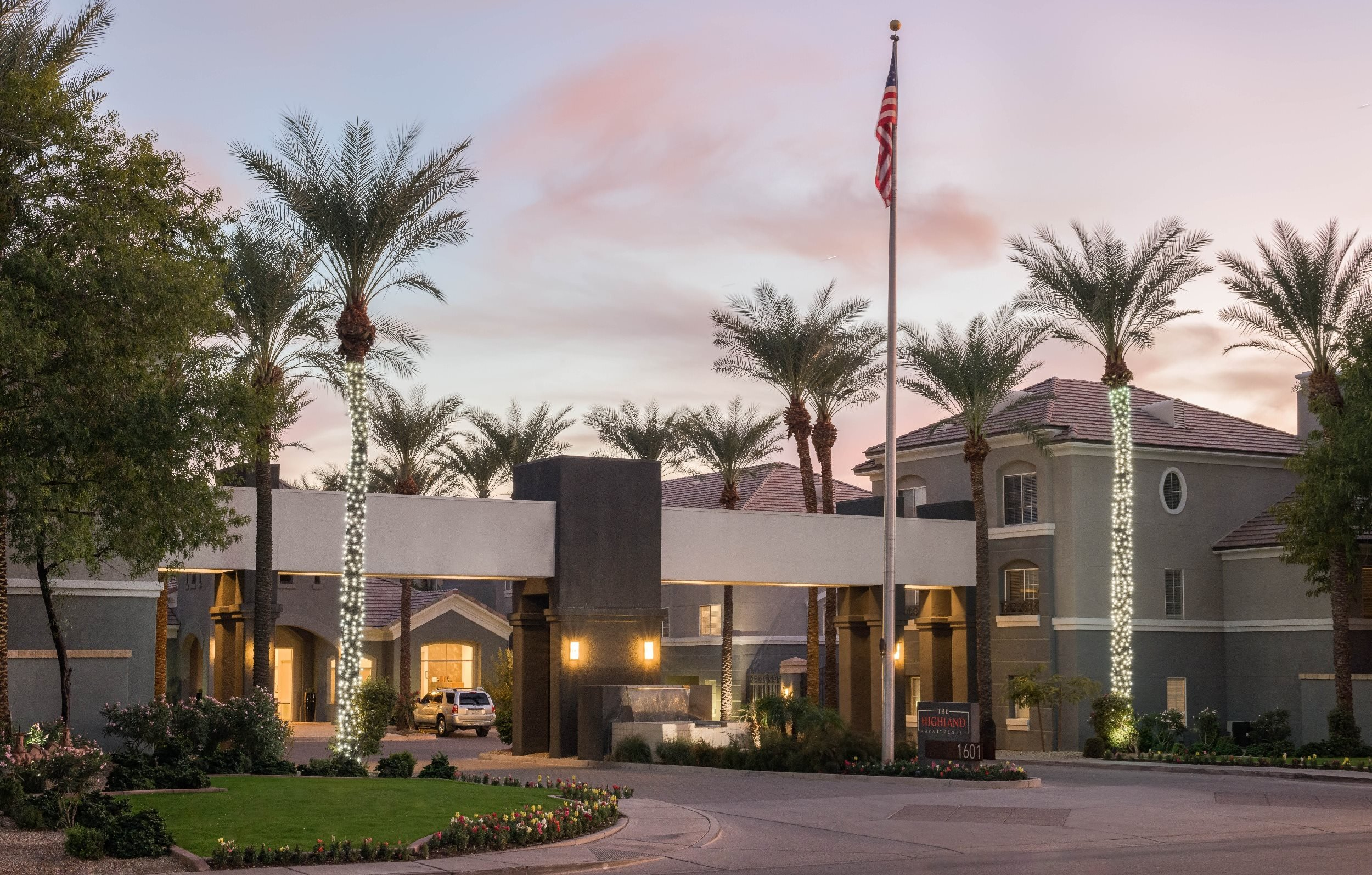 The Highland Apartments front entrance with lit palm trees and grass