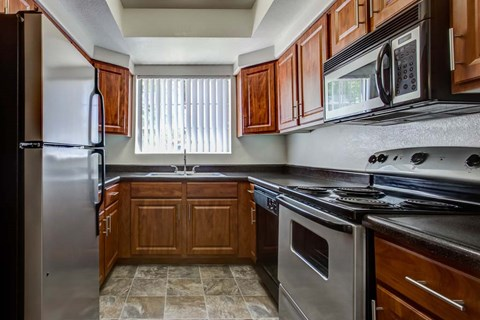 The Palms Apartments Kitchen with dark wood cabinets and stainless appliances