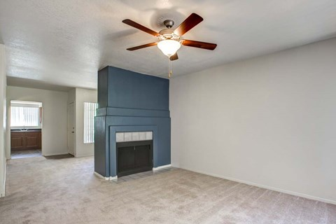 The Palms Apartments Living Room with wall to wall carpet, and dark blue fireplace