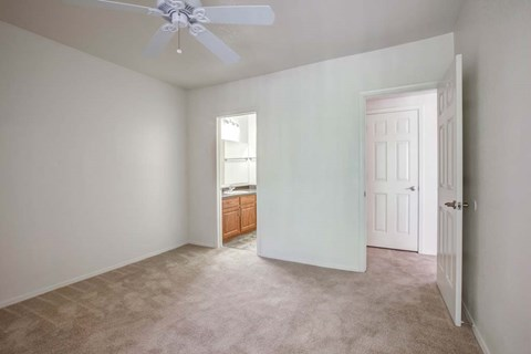 The Palms Apartments Bedroom with wall to wall carpet and ceiling fan