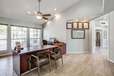 The Palms Apartments brown leasing office desk with two chairs, and light tan hardwood style flooring