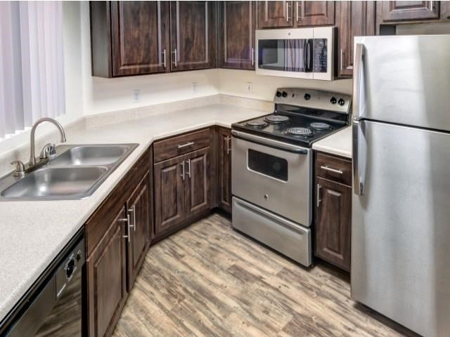 Ingleside Apartments kitchen with dark brown cabinets, white counter tops and stainless steel appliances