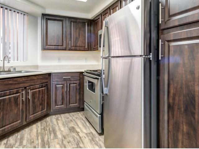 Ingleside Apartments kitchen with light brown floors, dark brown cabinets and stainless steel appliances