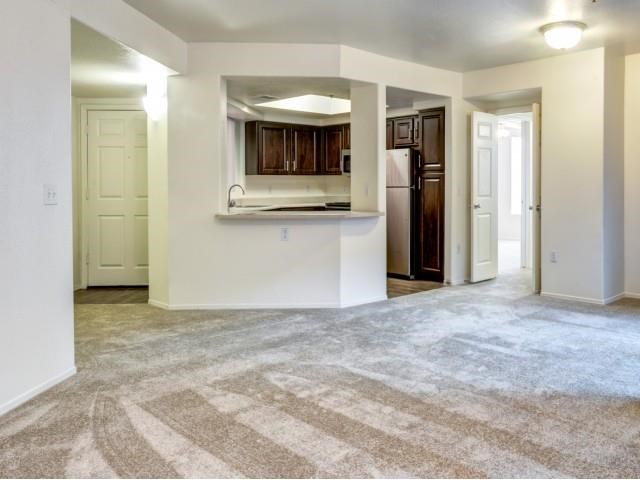 Ingleside Apartments Living Room with wall to wall carpet and kitchen by the front door