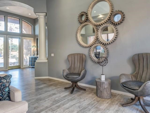 Ingleside Apartments Clubhouse sitting area with brown leather chairs, mirrors and light brown hardwood floors