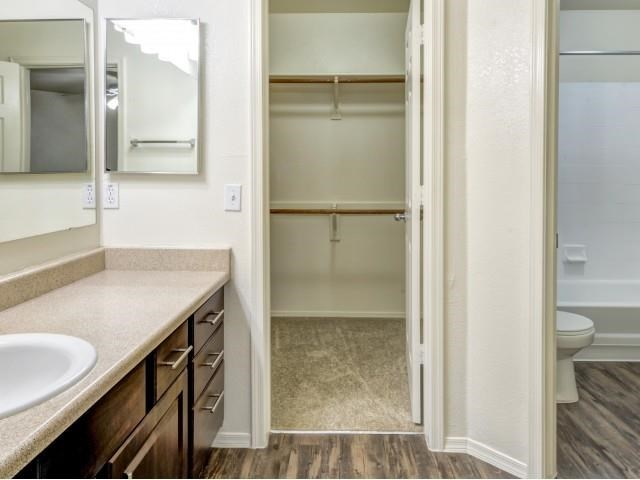 Ingleside Apartments Bathroom  with brown cabinets, beige counter tops and large walk in closet