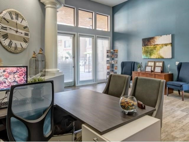 Ingleside Apartments Leasing Office desk with side chairs and blue accent wall