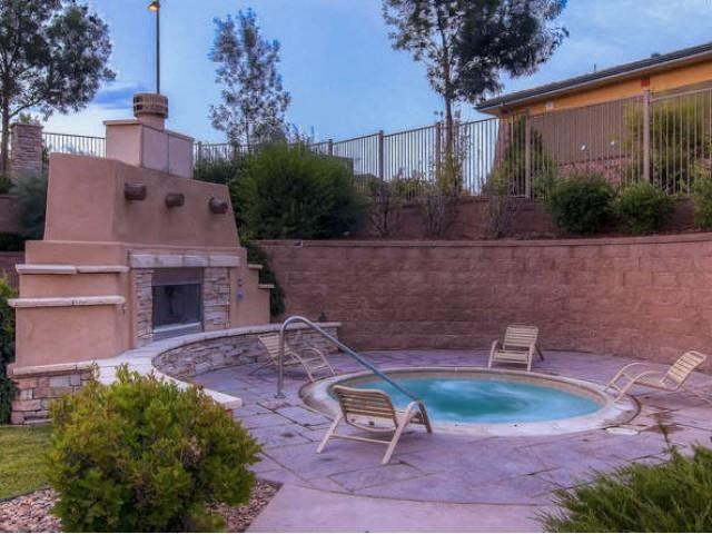 Sonoma Resort at Saddle Rock hot tub with brick retaining wall and four chairs around the hot tub