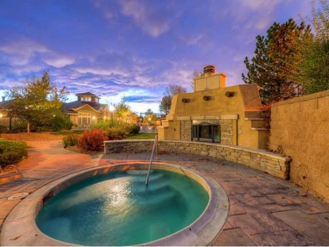 Sonoma Resort at Saddle Rock hot tub with outdoor fireplace, and clubhouse in background at sunset