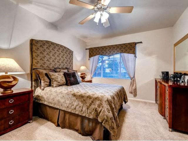 Sonoma Resort at Saddle Rock bedroom with brown patterned headboard, side table and chest of drawers, wall to wall carpet and window