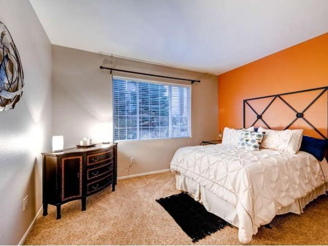 Sonoma Resort at Saddle Rock bedroom with orange accent wall, wall to wall carpet, brown dresser and white linen on bed