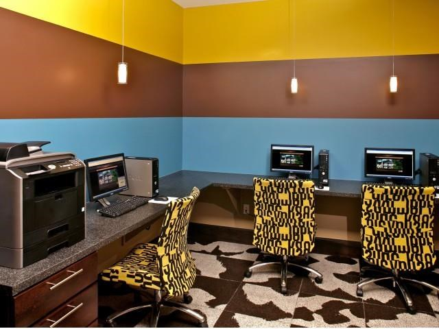 Copper Flats Apartments business center with blue, brown, and yellow striped walls, patterned chairs with computers and brown and white carpet