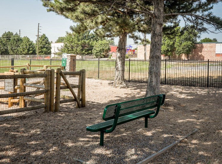 Bark Park with shady trees, gravel, and bench
