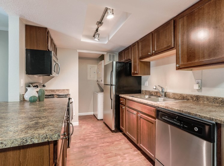 cherry cabinets, faux granite countertops, and stainless steel appliances
