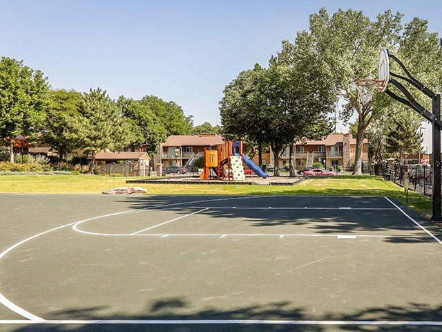 Copper Flats Apartments green outdoor basketball court with kids playground and grass in the background