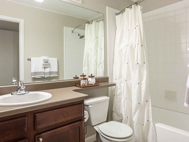 Copper Flats Apartments bathroom with brown cabinet, beige countertoo, and bathtub/shower with white shower curtain