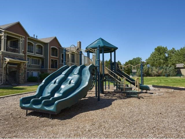 playgound with three green slides and community in the background