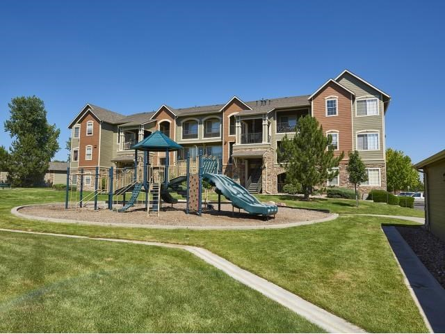playground with green slide with apartments in background
