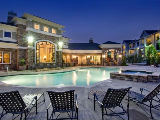 pool at twilight with black lounge chairs, and lit clubhouse