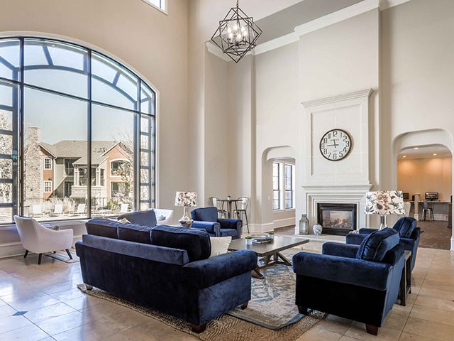 clubhouse with blue couches, fireplace and large windows facing the pool
