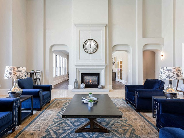 clubhouse seating area with blue chairs and fireplace, and high ceilings with white walls