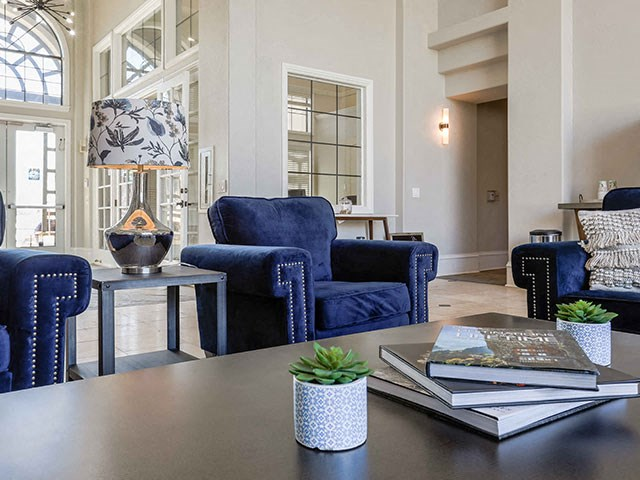 Champions Park Apartments clubhouse coffee table with books, succulent and large navy chairs