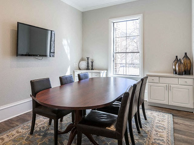 Champions Conference room with tv, brown table, chairs and window