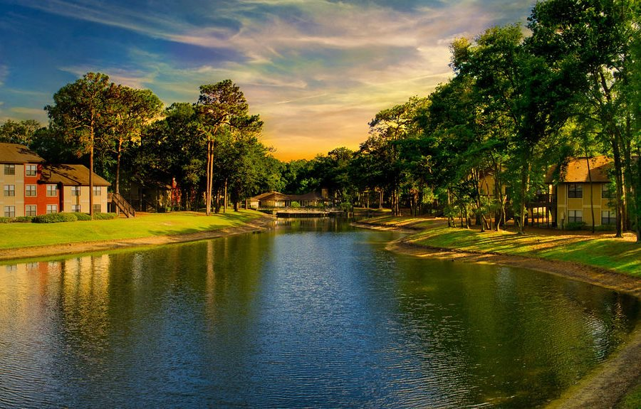 Northlake Apartments Jacksonville, Florida lake between apartment buildings, manicured landscaping and lush trees at sunset